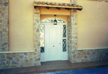 Puerta de entrada con adornos en forja y voladizo con teja